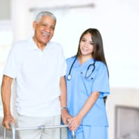 caregiver and senior man smiling